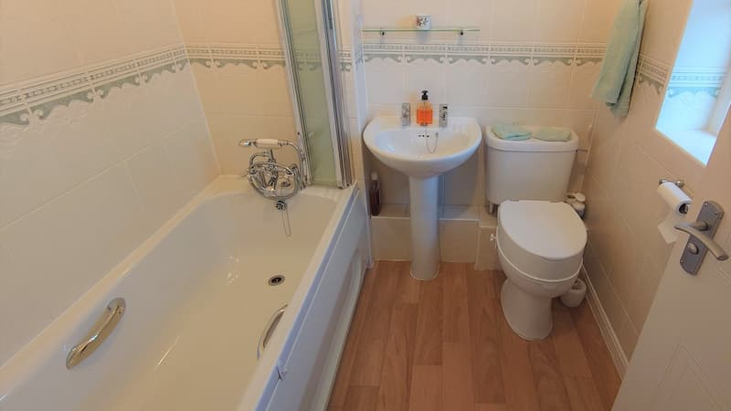 bathroom with bath, screen, toilet and sink with wooden flooring