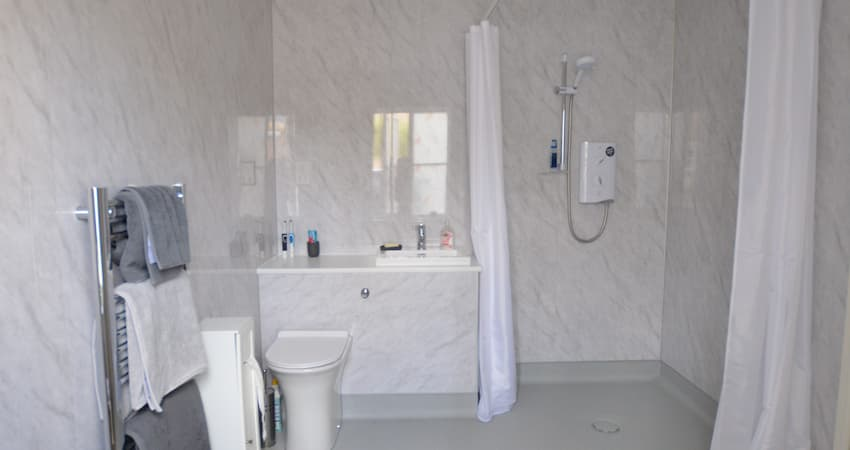 White and grey wet room with shower toilet shower curtains and sink