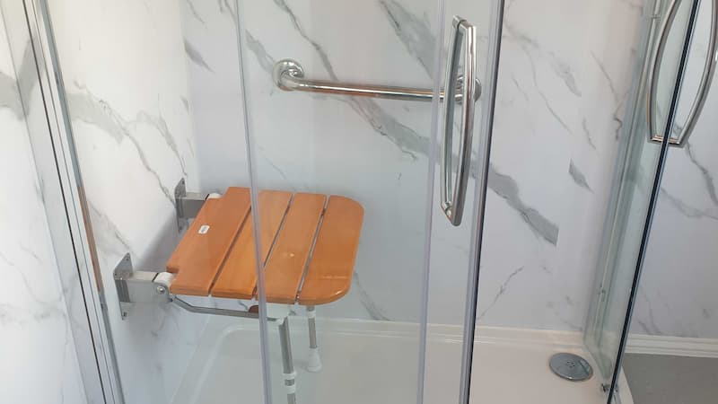 Walk in light grey shower with handrails and seat