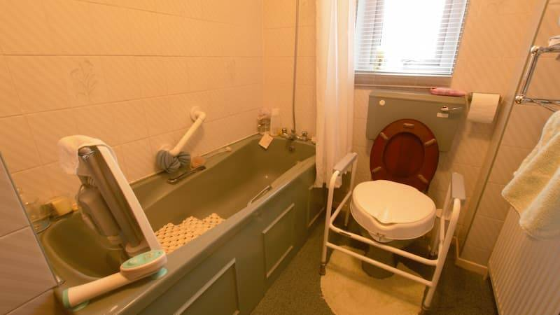 Bathroom with bath, handrails, shower curtain and supported toilet
