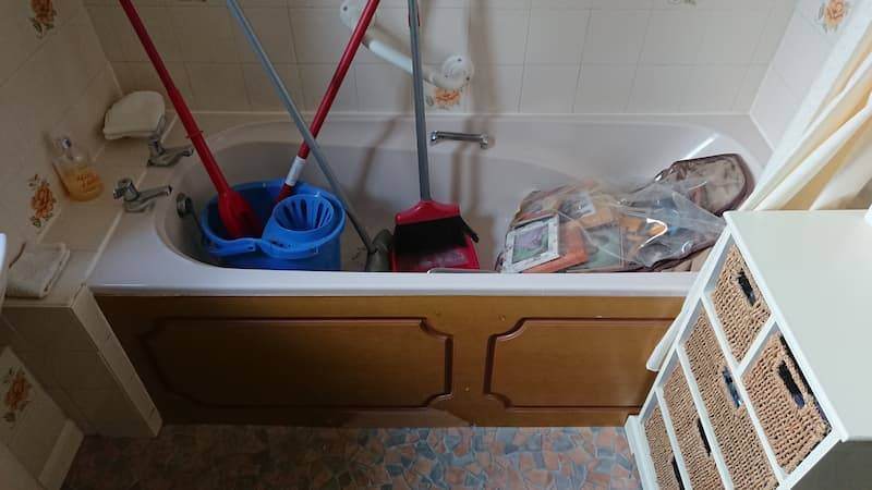 small bathtub filled with mops and brooms